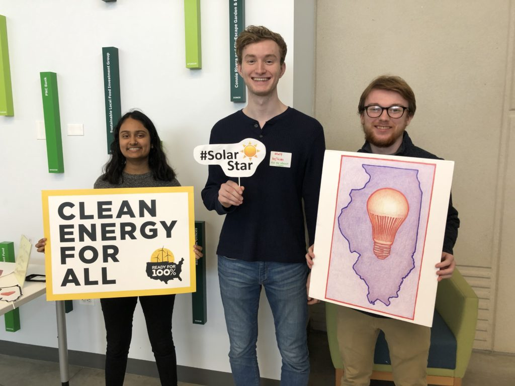 "3 young adults hold posters and signs about clean energy. The left reads ""Clean Energy For All"", the middle reads ""Solar Star"" and the right image is an outline of the state of Illinois with a lightbulb in the center"
